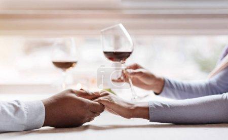 Photo pour Dîner romantique pour deux. Jeune couple afro-américain joyeux et paisible assis dans le restaurant et ayant la date tout en exprimant l'amour et en tenant des verres à vin - image libre de droit