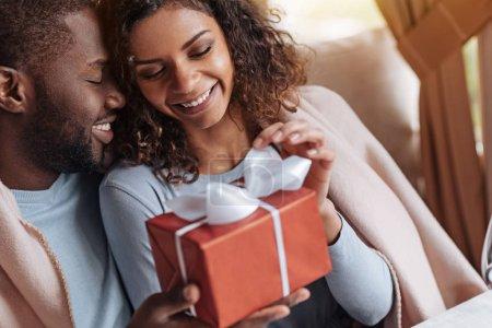 Photo pour Belle journée avec mon âme soeur. Joyeux sourire heureux afro-américain obtenant la boîte avec le présent et assis dans le café avec son petit ami, tout en étant recouvert de la couverture - image libre de droit