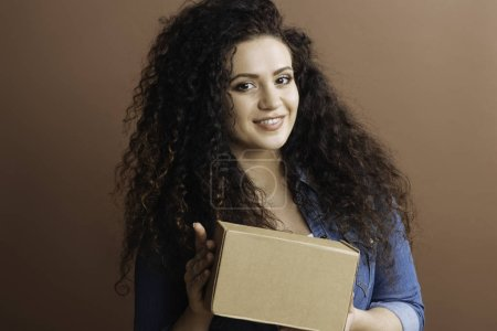 Delighted female holding box in both hands
