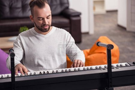 Photo for Hobby is important. Attractive focused physically challenged person enjoying spending time in his apartment practicing his music skills on the piano - Royalty Free Image