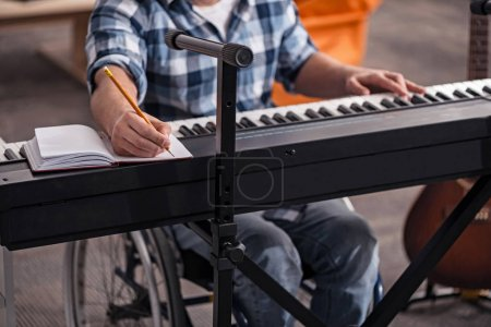 Handicapped musician writing down notes