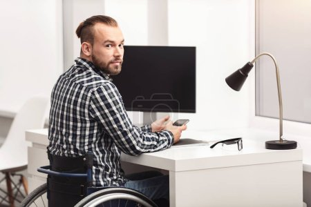 Photo for Getting things done. Handsome positive disabled man sitting at the table in his wheelchair while using his smartphone and planning something - Royalty Free Image