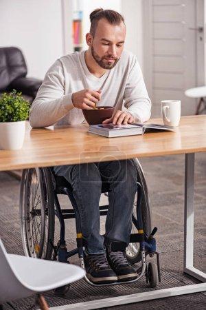 Photo pour Nourrir le corps et l'esprit. bel homme intelligent intéressé prendre le petit déjeuner et lire un livre intéressant tout en étant assis dans un fauteuil roulant à la table - image libre de droit