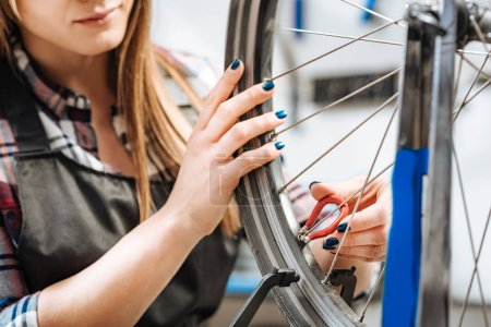 Involved woman repairing the bicycle in the garage