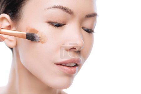 Nice asian woman applying several layers of liquid foundation