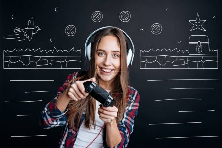 Cheerful delighted young woman playing video games