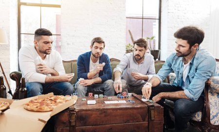 Good looking brutal men playing cards
