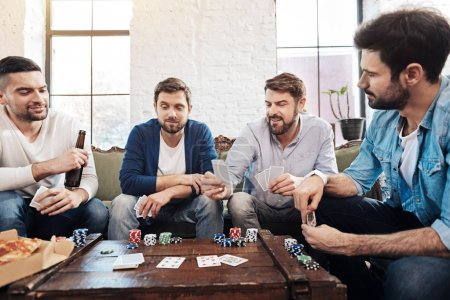 Good looking male friends playing poker