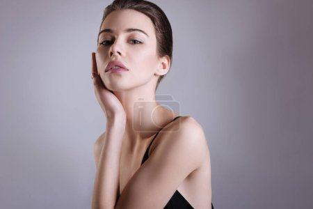 Delicate lady posing on a grey background