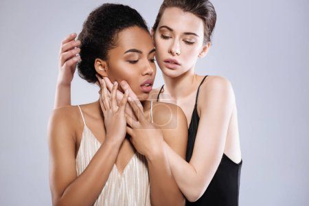 Photo for Magnetic tension. Lovely talented professional models doing a photoshoot together in a studio while one of them holding her friend closely to her - Royalty Free Image