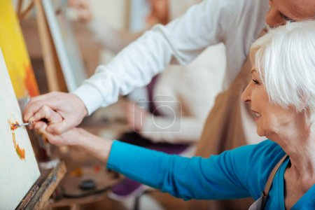 Artist helping his elderly colleague in painting class