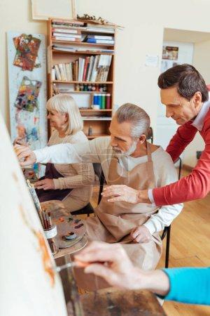 Talented artist helping elderly man in painting studio