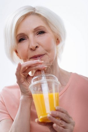 Delighted blonde woman posing with orange juice