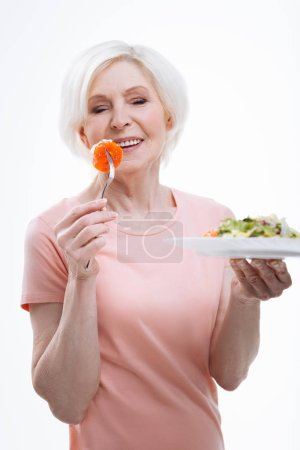 Positive delighted woman getting satisfaction from eating