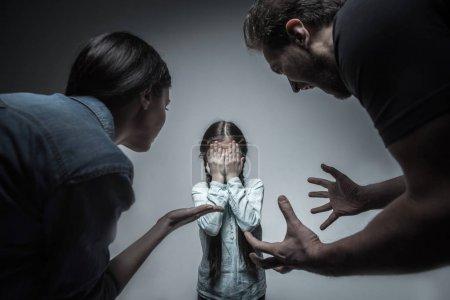 Photo pour Vous devriez changer. Deux adultes en colère portant des vêtements casual foncés garder les mains en l'air en pleurant sur leur fille, qui se tient debout entre eux - image libre de droit