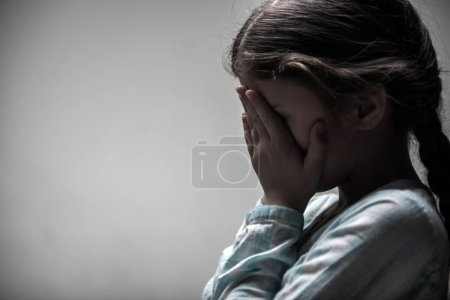 Photo for Want to cry. Young thoughtful girl wearing casual clothes keeping her hands on her face standing isolated on grey - Royalty Free Image