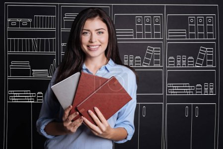 Cheerful female student holding notebooks.
