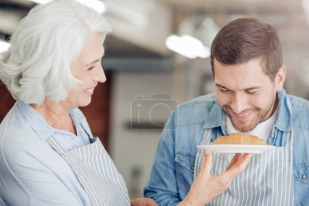 Positive man going to cook croissant with her grandmother