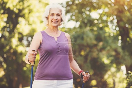 Delighted smiling woman exercising in the park