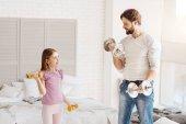 Muž stojící zobrazeno cvičení pro dceru