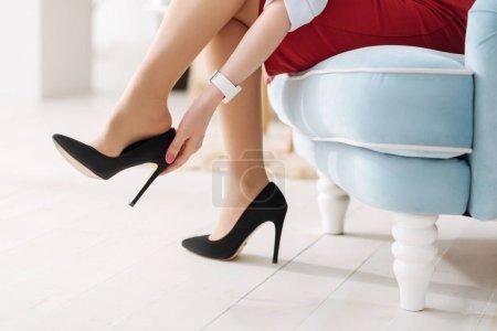 Foto de Volviendo a casa. Primer plano de hermosa mujer agradable quitándose elegantes zapatos de tacón alto mientras vuelve a casa - Imagen libre de derechos