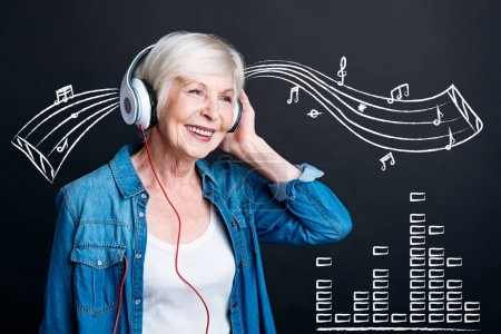 Delighted aged woman wearing headphones