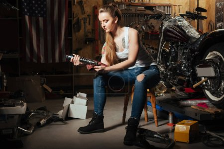 Cute young woman holding spare part from bike