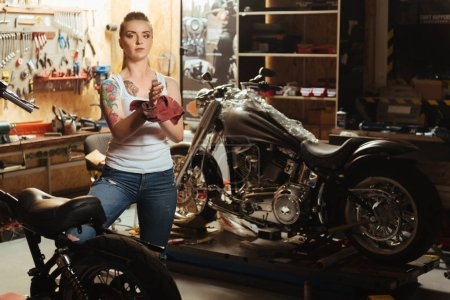Serious girl with tattoo posing in workshop