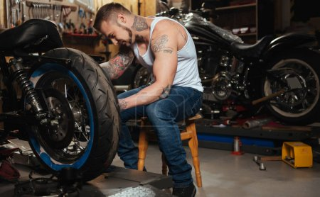 Positive delighted brutal biker fixing wheel