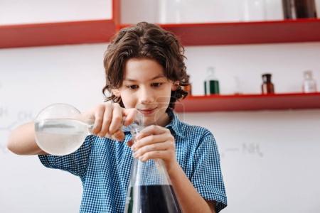 Boy mixing chemical liquids