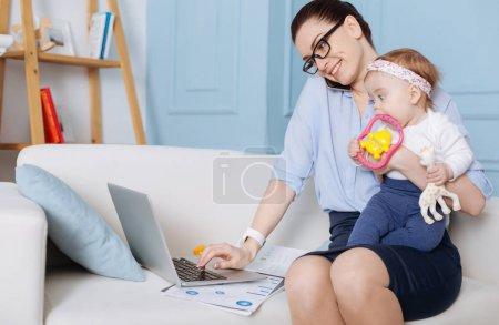 Photo pour Capable de tout. Mère brillante et élégante qui travaille dur appelant quelqu'un sur son téléphone portable et lisant les données tout en tenant son enfant dans son autre main - image libre de droit