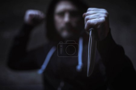 Dangerous criminal holding up knife