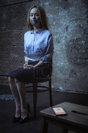 Photo for Trapped helpless miserable girl trying figuring out who calling while sitting in a dark room tied up to a chair - Royalty Free Image