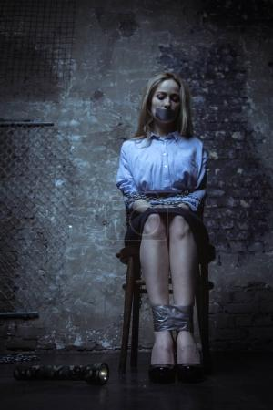 Girl sitting on chair tied up