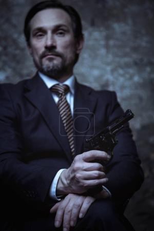 Businessman keeping pistol in hand
