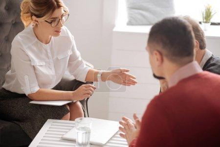 Photo pour Thérapie de couple. Professionnel agréable psychologue intelligent assis en face de ses patients et leur expliquant leur problème tout en ayant une session psychologique - image libre de droit