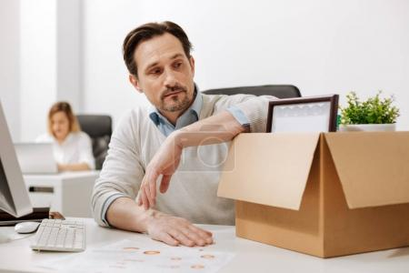 Thoughtful manager holding the box and sitting in the office