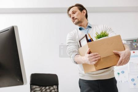 Fired employee carrying the box and leaving the office