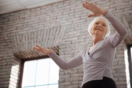 Elderly woman dancing in ballroom