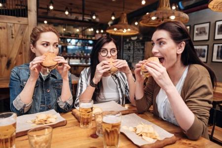 Positive delighted friends eating unhealthy food