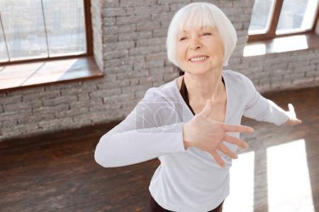 Charming elderly woman dancing at the ballroom
