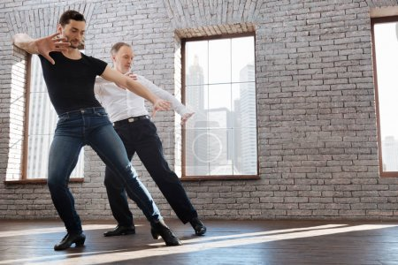 Charismatic dance couch teaching aging man tango at the ballroom
