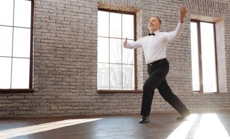Upbeat senior man performing classical dance at the ballroom