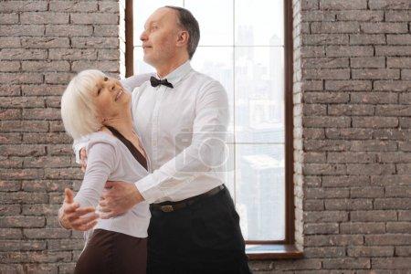 Lively elderly dance couple enjoying tango at the ballroom