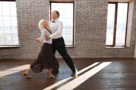 Photo pour Plein d'harmonie. Talentueux couple de personnes âgées flexible et gracieux dansant dans la salle de bal tout en améliorant les compétences en danse et en tangoing - image libre de droit