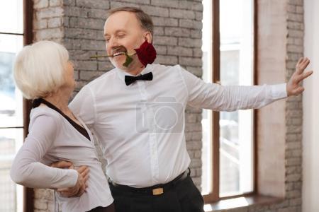 Photo pour J'essaie de vous séduire. Charismatique passionné inspiré vieil homme tanguer avec la femme âgée dans le studio de danse tout en démontrant des compétences en danse et tenant rose avec ses dents - image libre de droit