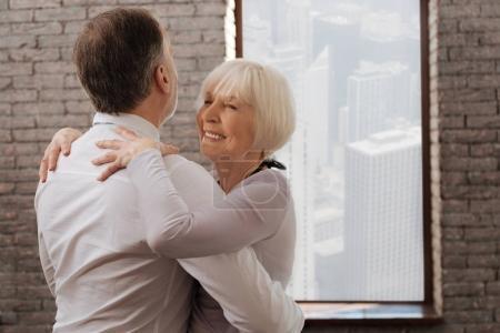 Photo pour Je me sens libre. Charismatique couple paisible de danse du vieillissement heureux tanguer dans le studio de danse tout en démontrant des compétences en danse et en exprimant la positivité - image libre de droit