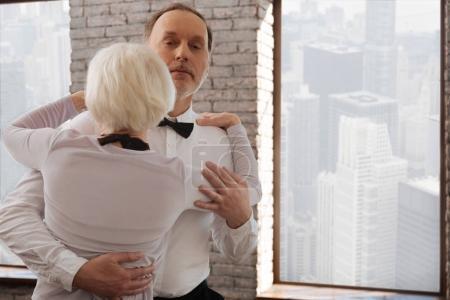 Peaceful elderly dance couple waltzing in the dance studio