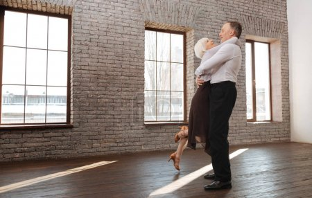 Delighted retired couple enjoying waltz in the dance studio