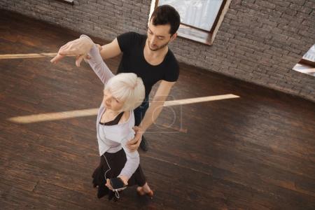 Athletic dance teacher instructing retired woman in the ballroom